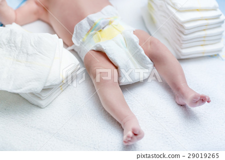 Feet of newborn baby on changing table with 29019265