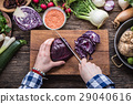 Women hands is slicing cabbage on wooden board. 29040616