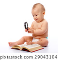 Little child play with book and magnifier 29043104