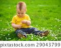 Little boy is sitting on green meadow 29043799