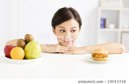 woman  choice between healthy and harmful food 29053338
