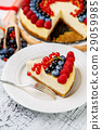 Raspberry and blueberry cheesecake on wooden table 29059985