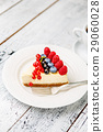 Raspberry and blueberry cheesecake on wooden table 29060028