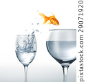 Gold fish jumping from a glass of water, to a larger one. 29071920