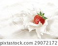Strawberry falling into a sea of milk, causing a splash. 29072172