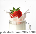 Strawberry falling into a glass mug full of milk, splashing. 29072208