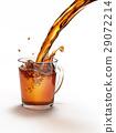 Tea pouring into a glass mug splashing. 29072214