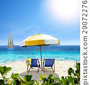 Beautiful beach with white sand, two chairs, umbrella and a sailing boat in the sea. 29072276