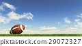 American football ball, on the grass, with fluffy couds sky in the background. 29072327