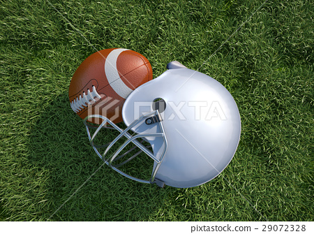 American football helmet and ball, on the grass. Close up. 29072328