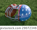 American football helmet and ball, on the grass. Close up. 29072346
