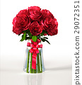 Glass vase full of big red roses, with ribbon. On white reflective surface and background. 29072351