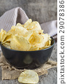 Potato chips in bowl on wooden background. 29078386