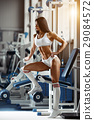 Muscular brunette woman seductive posing  in gym. 29084572