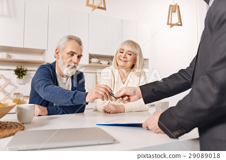 Delighted aged couple signing loan contract at 29089018