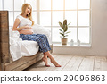 Happy pregnant woman sitting in bed 29096863