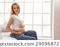 Attractive pregnant lady sitting on side of bed 29096872