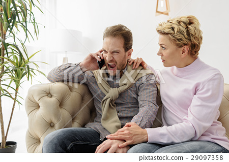 Irritated guy speaking on smartphone near his wife 29097358