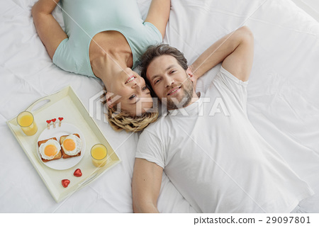 Happy lovers lying on bedding with relaxation 29097801