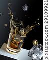 Ice cube splashing into a glas of liquid. 29109921