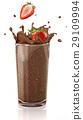 Strawberries splashing into a chocolate milkshake glass. 29109994