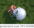 American football helmet and ball, on the grass. Close up. 29110208