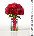 Glass vase full of big red roses, with ribbon. On white reflective surface and background. 29110250