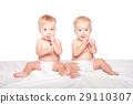 Cute twins babies with spoons 29110307