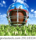 American football helmet over the oval ball, on the grass. Frontal Close up view. 29110334