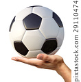 Man's hand holding a soccer ball on palm. 29110474