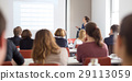 Woman giving presentation in lecture hall at 29113059