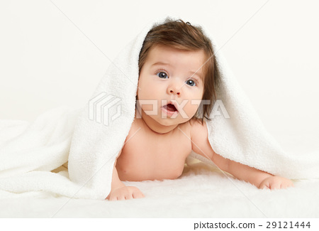 Baby lie on white towel in bed, yellow toned 29121444