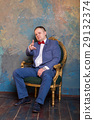 Imposing mature man in elegant suit sitting on a 29132374