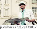 Young man holding a road map at the retro car 29139017