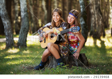 Two hippie girls with guitar in a summer forest 29139468