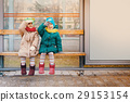 Two girls sit at the bus stop 29153154