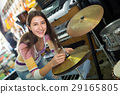Adult girl choosing drums and accessories 29165805