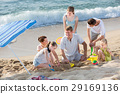 Laughing family playing games on beach on weekend 29169136