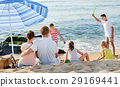 Couple relaxing on beach while their kids playing active games 29169441