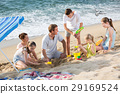 family with four kids relaxing on beach. 29169524