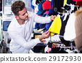 male customer examining knit caps in sports store 29172930