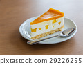 A piece of mango cheese cake on wooden background 29226255