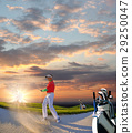 Man playing golf against colorful sunset 29250047