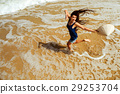happy girl jumping on the beach top view 29253704