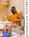 Man in gas mask sitting on toilet and reading book 29254881