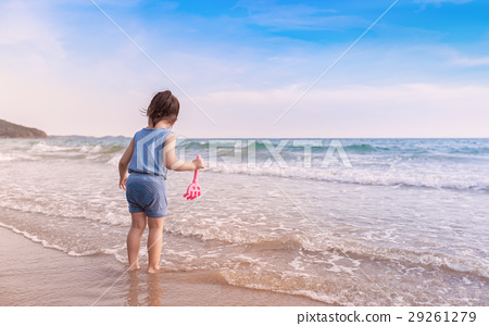 little girl playing on the beach in sunset 29261279