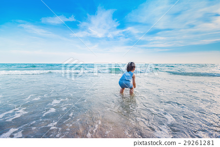 little girl playing on the beach in sunset 29261281