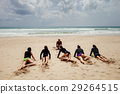 surfer instructor with surfer girls on beach 29264515