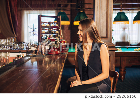beautiful young woman sitting at the bar talking 29266150