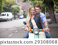 Happy young couple by a vintage scooter on street 29308068